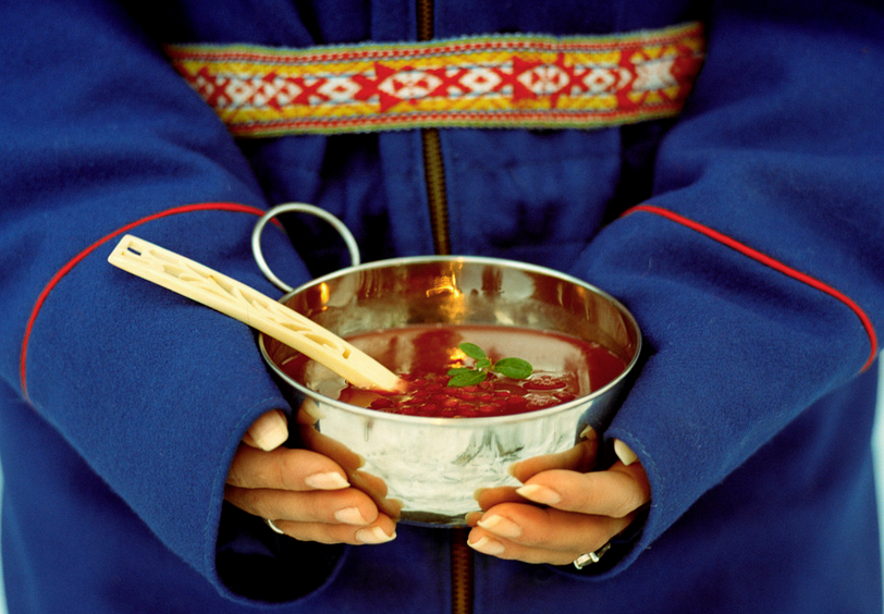 Kvinne i samekofte holder skål med tyttebærsuppe i fanget. Foto.