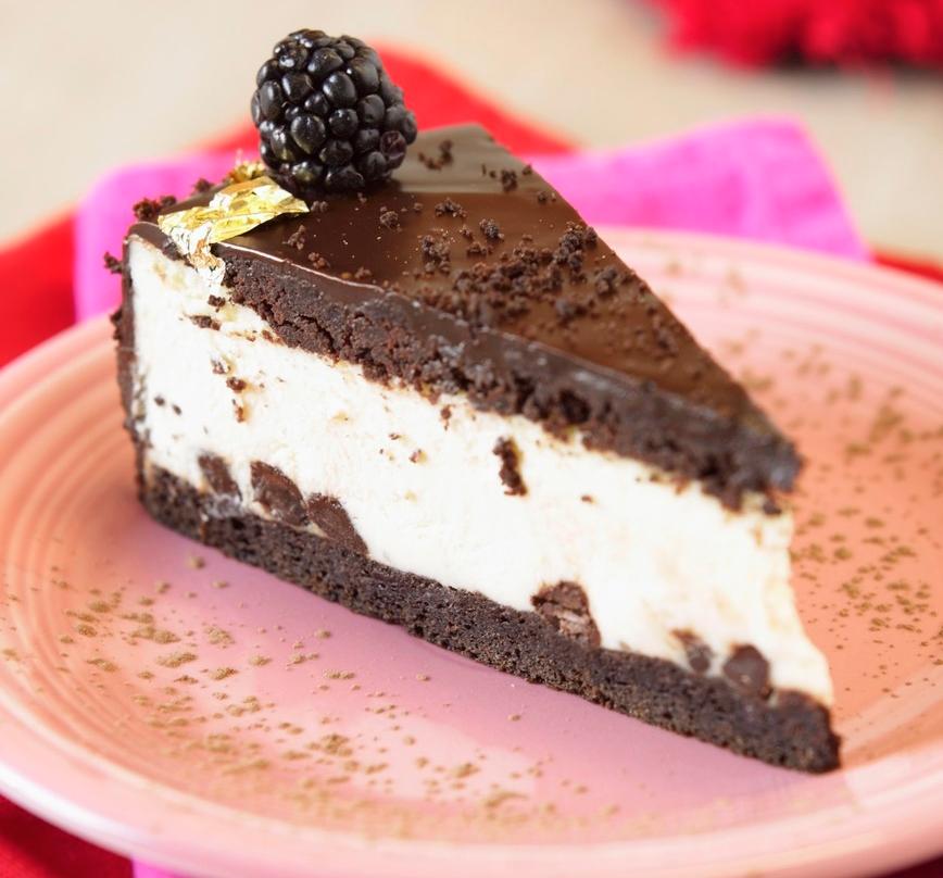 Et stykke sjokoladekake med hvitt fyll og bjørnebør til pynt. Foto