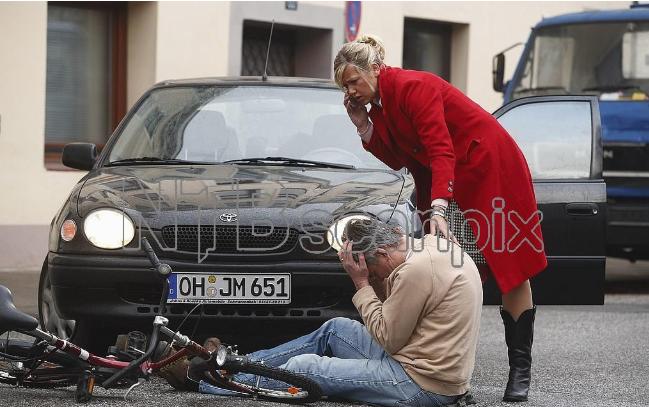 En dame ringer mens hun holder hånden på skulderen til en skadet person som sitter på bakken. Foto.
