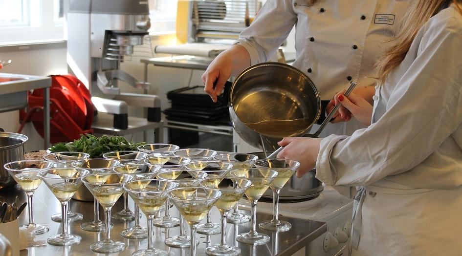 To elever som sjenker opp aperitiff i glass. Foto.