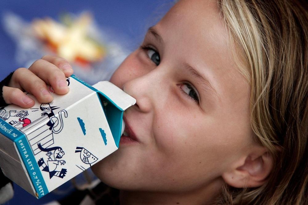 En jente som drikker lettmelk av en kartong. Foto.
