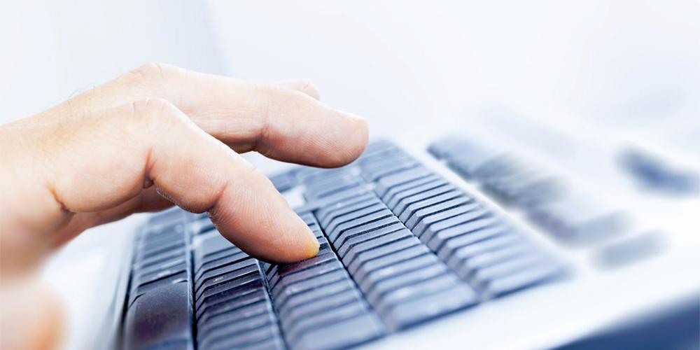 Nærbilde av en som skriver på tastatur. Foto.