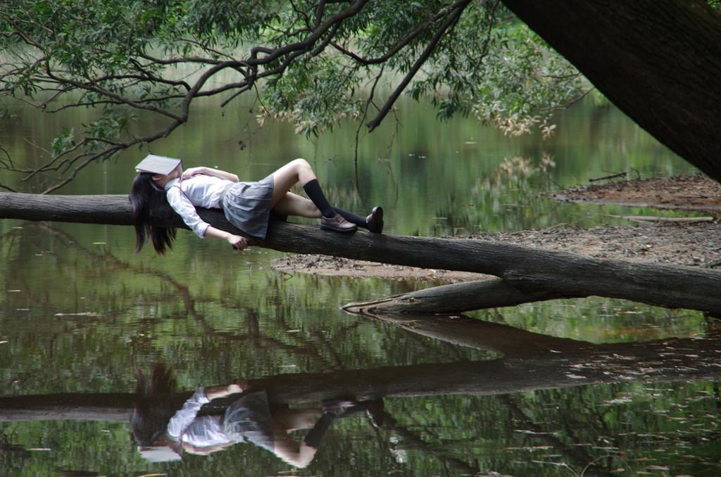 Jente sover med bok over ansiktet. Foto.