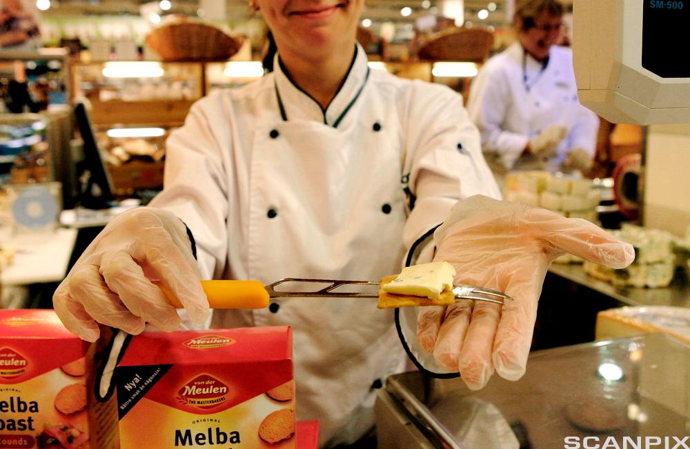 Kvinne i matvarebutikk deler ut smaksprøver av ost. Foto.