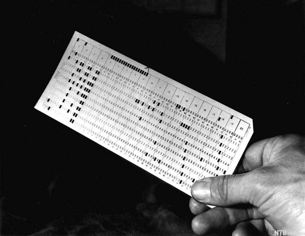 hånd som holder gammeldags hullkort for programmering. Foto