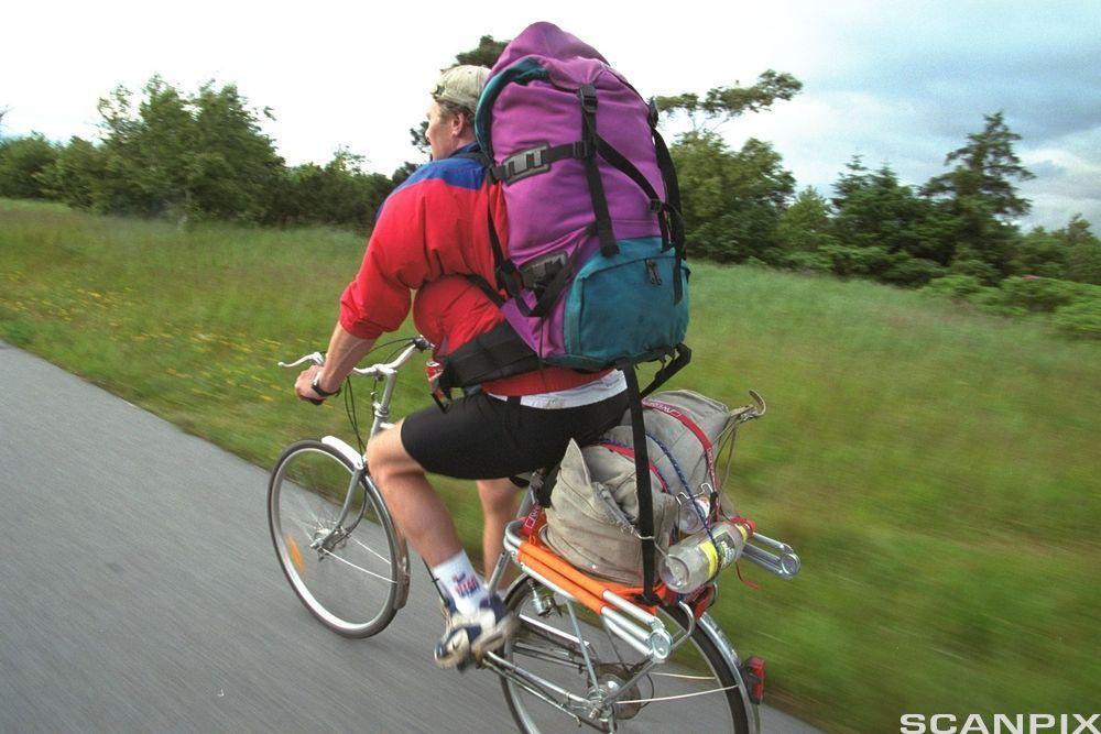 Syklist med stor ryggsekk på tur i landlige omgivelser. Foto.