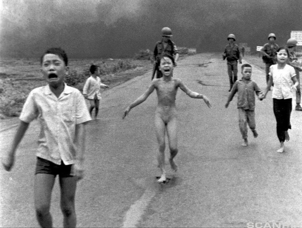 Barn på flukt etter napalmangrep under Vietnamkrigen, 1972. Én av jentene er naken. Soldater kan sees i bakgrunnen. Foto.