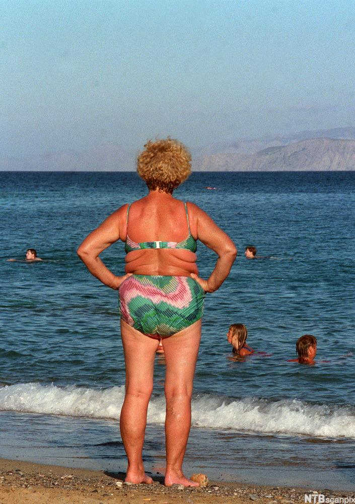 En middelaldrende, solbrun kvinne i bikini står med ryggen til og ser ut over havet. Foto.