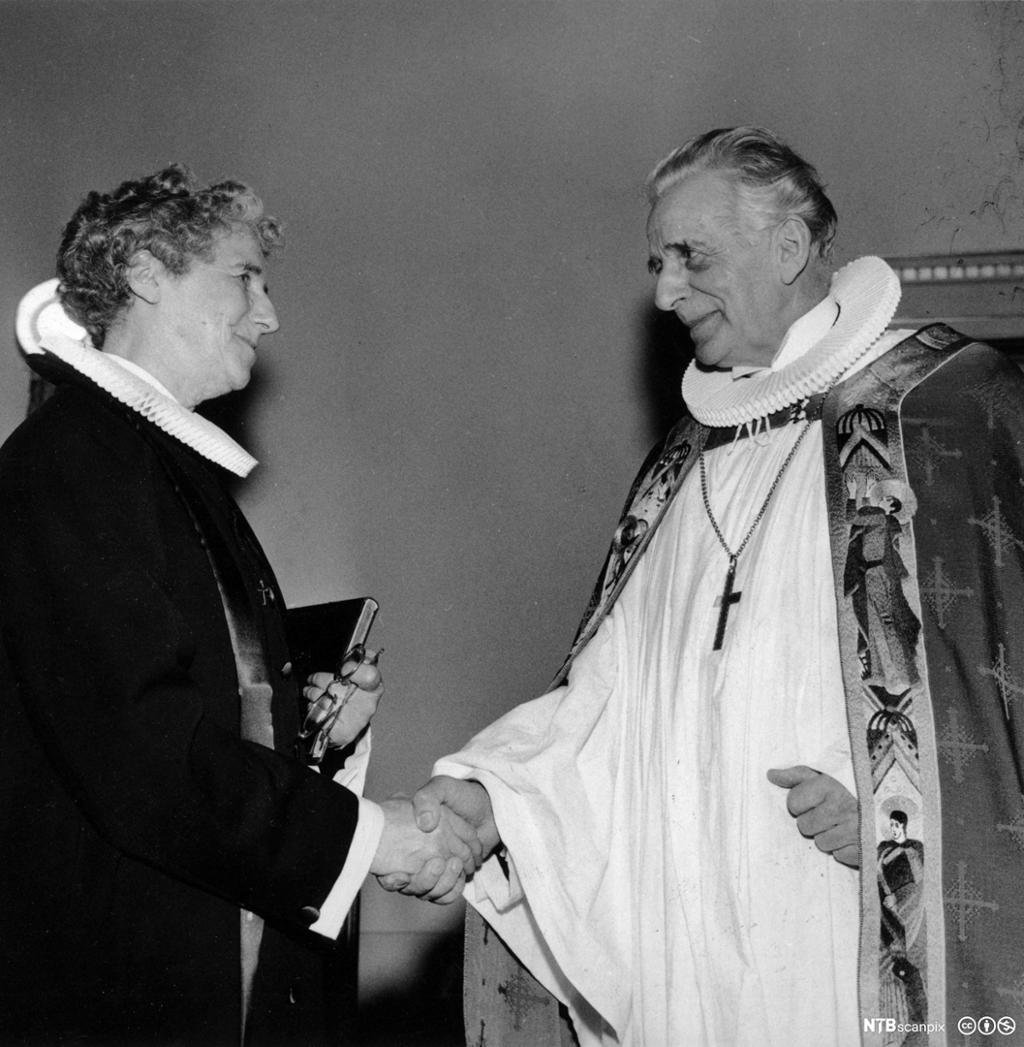 En kvinne i prestekjole og en mann iført biskopens embetsdrakt. De smiler til hverandre og tar hverandre i hånden. Svart/hvitt-foto.