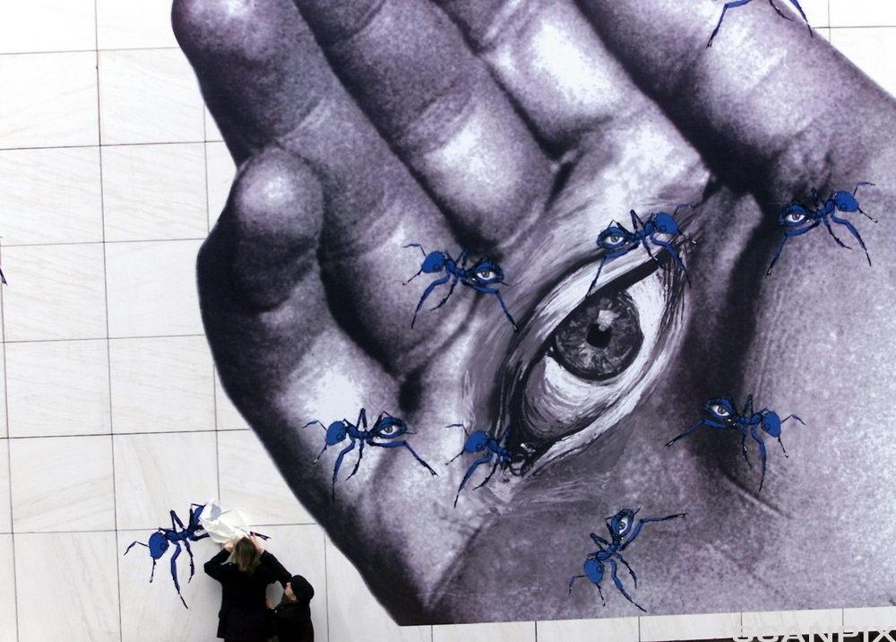 Hånd med øye og fluer. Foto.