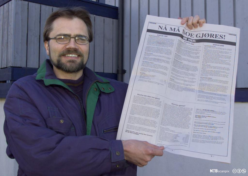 Mann som viser fram ei avisside med tittelen: Nå må noe gjøres! Tittelen er satt med veldig store bokstaver. Foto.