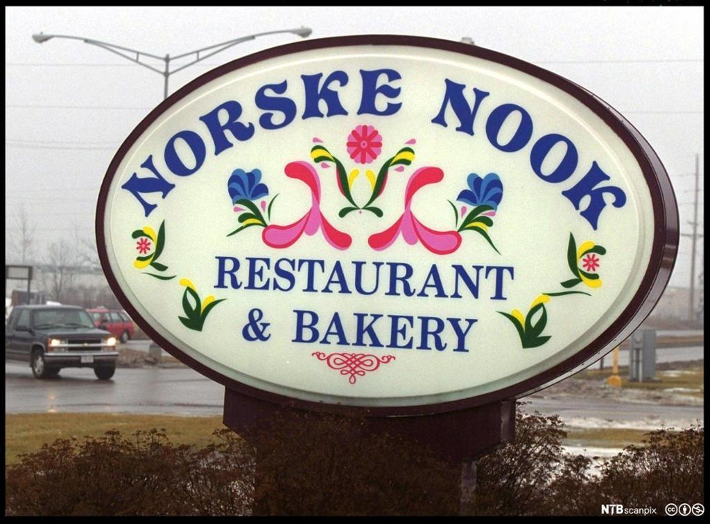 Stort lysskilt med reklame for en restaurant som blander norsk og amerikansk. Foto.
