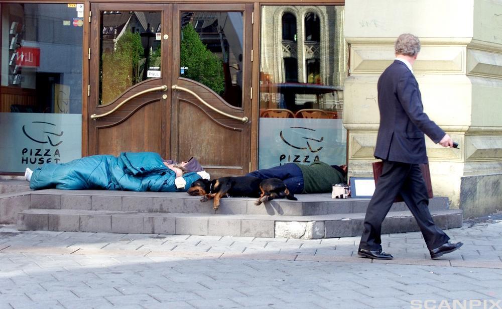 Mann går forbi to som ligger på gaten. Foto.