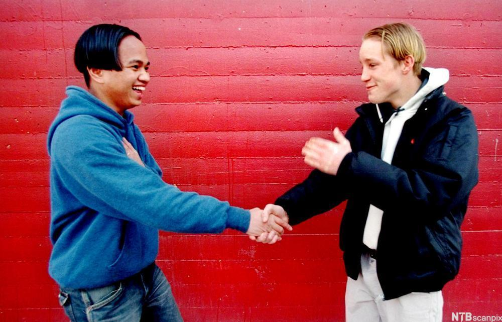 Gutter som håndhilser. Foto.