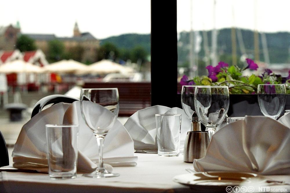 Et bord er dekket med hvit duk og hvite servietter. Foto.