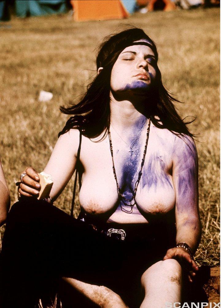 Toppløs dame med langt hår, pannebånd og kroppsmaling. Foto.
