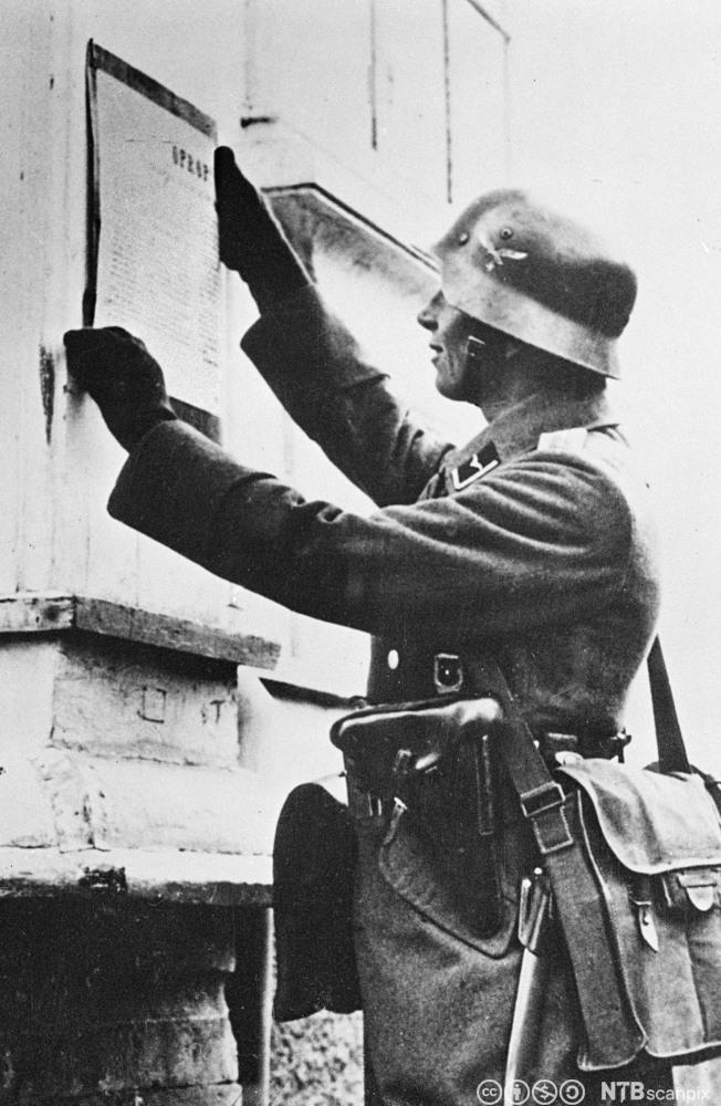 En tysk soldat slår opp kunngjøringen Falkenhorsts proklamasjon, i Trondheim 9. april 1940.