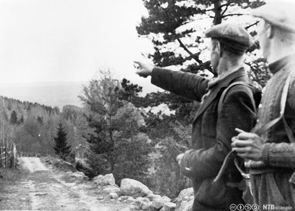 Norske flyktninger på vei over grensen til Sverige. Bildet viser to menn med ryggsekk.