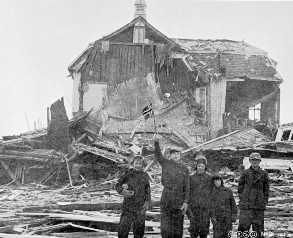skolebarn med norske flagg foran ruinene av en skole i Vadsø etter nedbrenningen av Finnmark. Januar 1945. Foto.