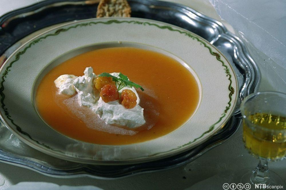 Moltesuppe i en suppeskål servert med en klatt rømme, friske molter og et mynteblad. Foto.