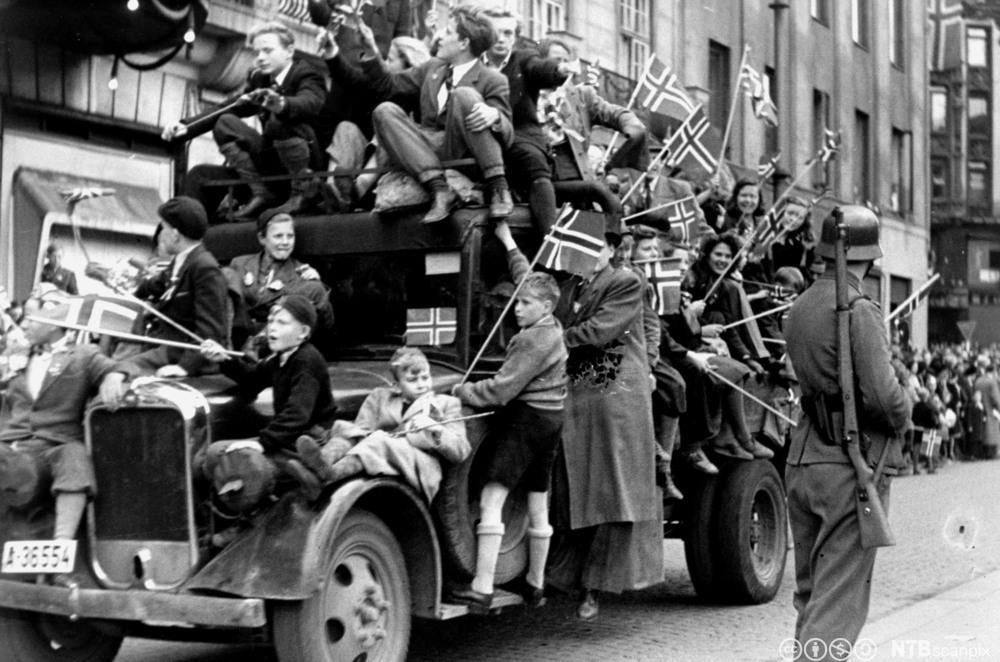 Lastebil full av jublende mennesker på Karl Johans gate, 8. mai 1945. Foto.