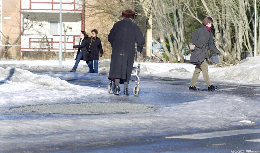 En dame som går med rullator på vinterføre. Foto.