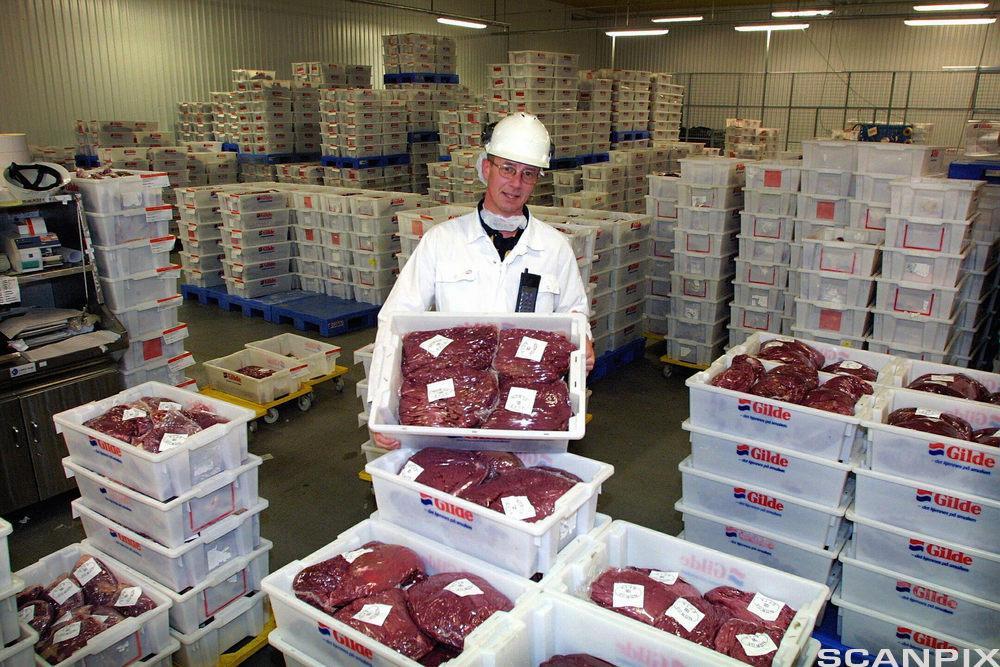 Larerarbeider viser frem kjøttvarer i plastkasser. foto.
