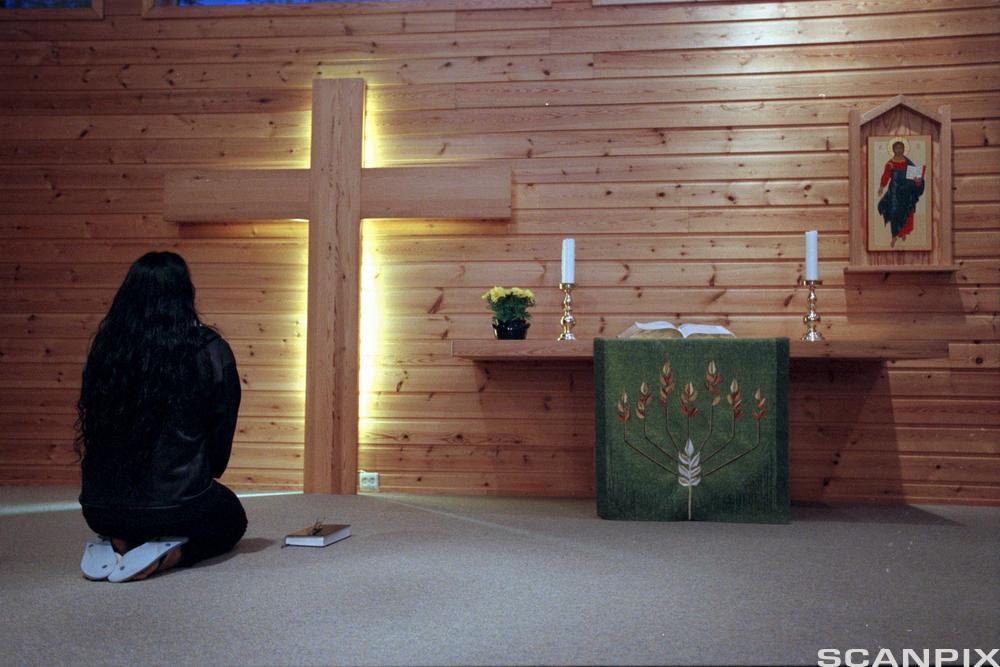 Kvinne sitter på huk foran et kors. Foto.