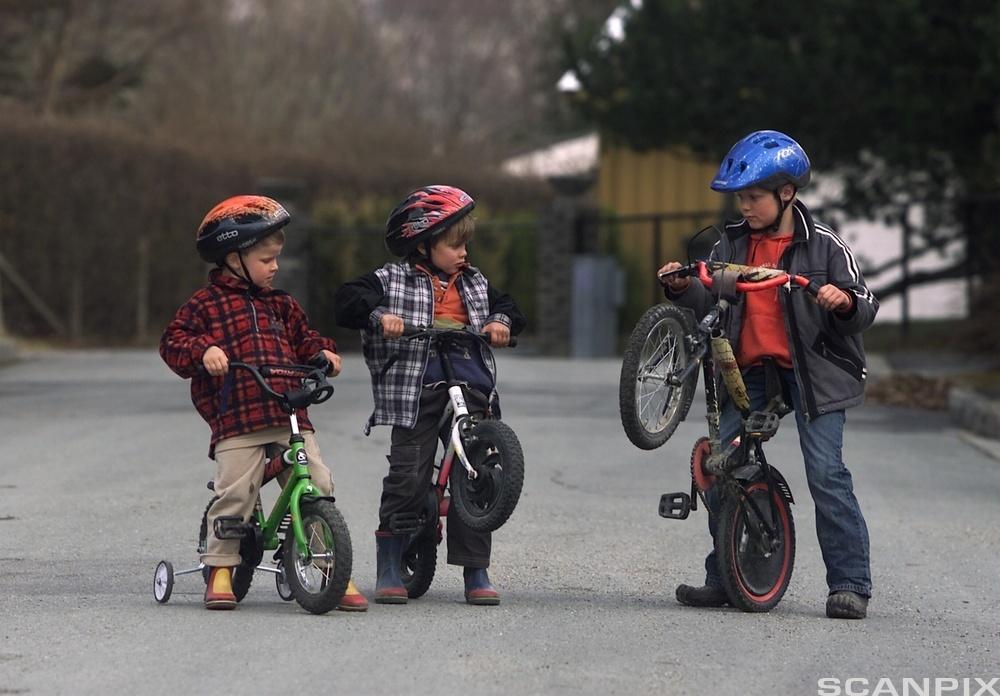 Barn sykler og har hjelm. Foto.