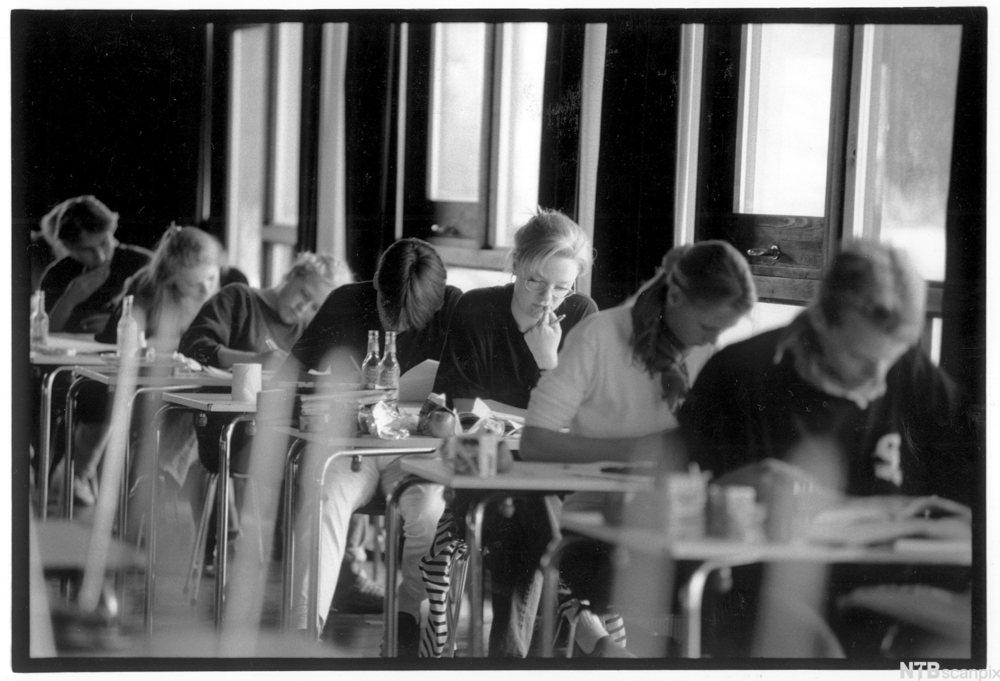 Rad med elever som sitter konsenterrt om oppgaver ved hvet sitt bord. foto.