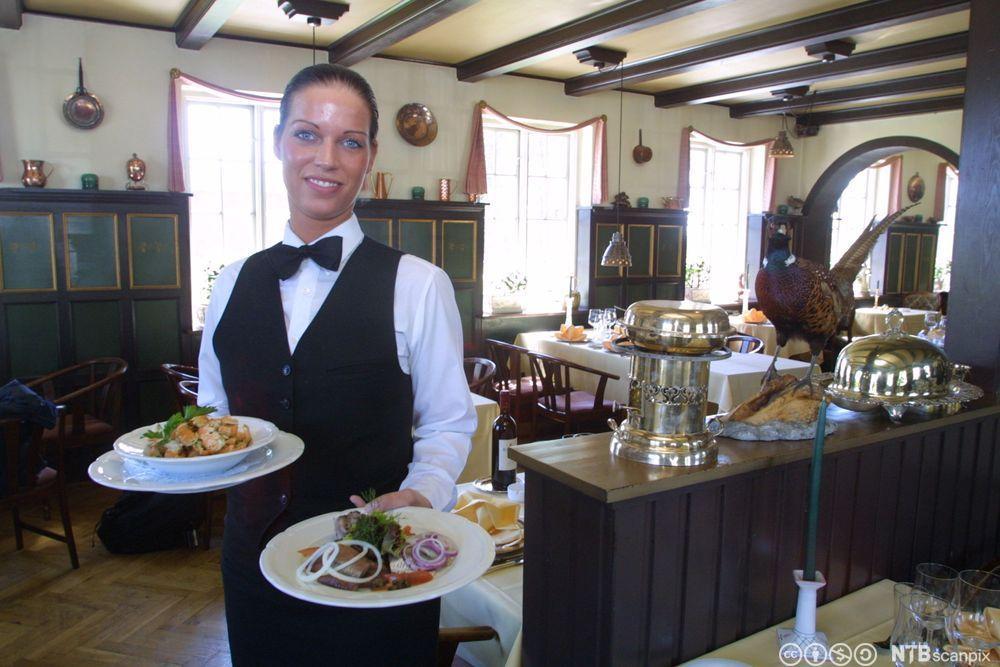 Servitør er på tur til gjesten med to tallerkener som er annrettet med mat. Foto