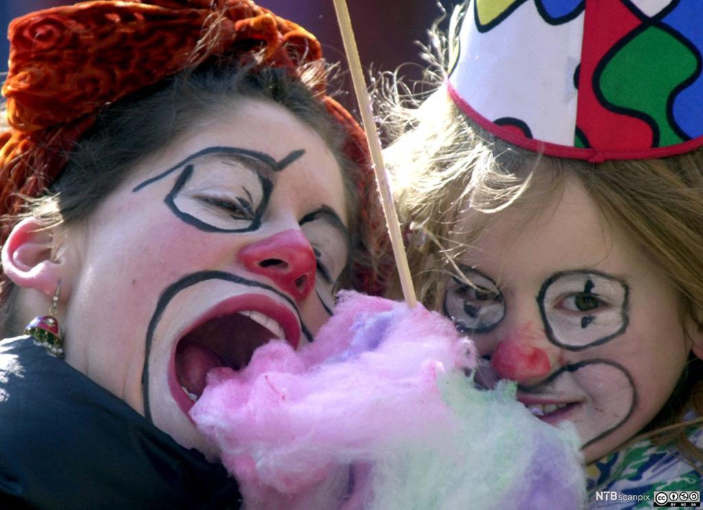 To jenter som er utkledd som klovner og spiser sukkerspinn. Foto.