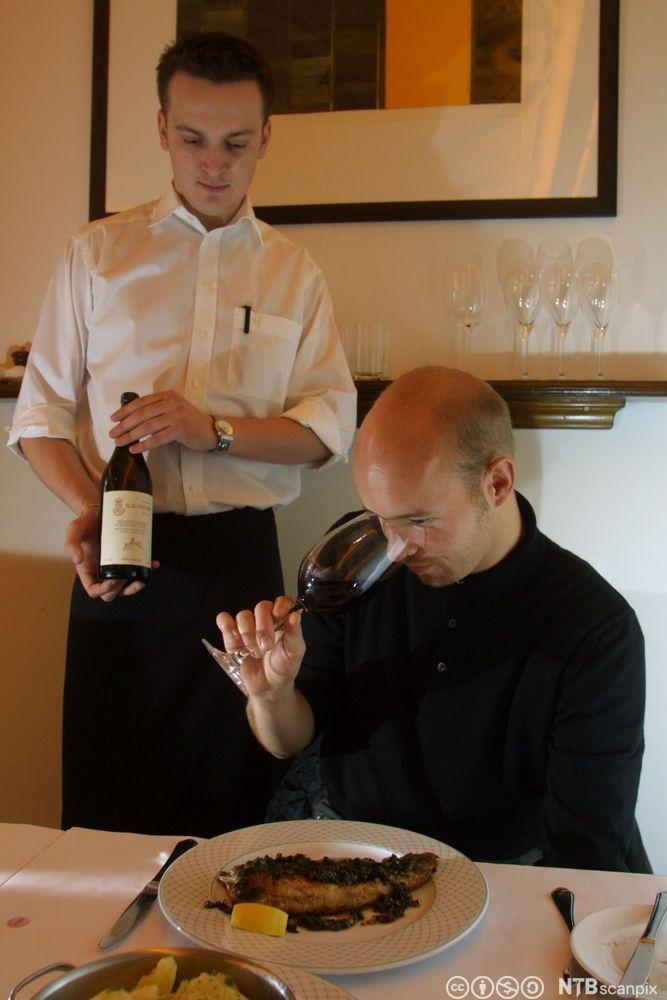Bilde av en vinkelner med en flaske, og en gjest som lukter på vinen. Foto. Foto.