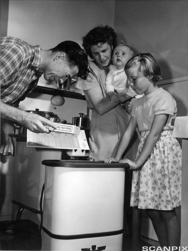 Bildet viser en familie med ny vaskemaskin i 1951