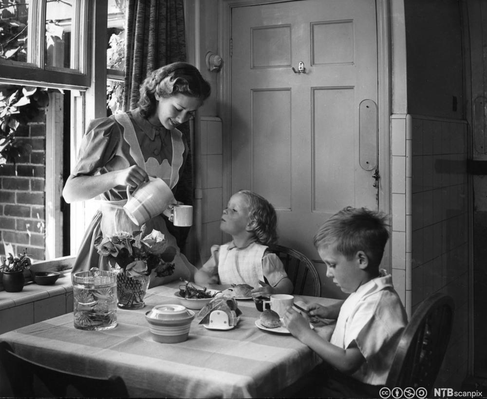 Husmor som serverer frokost til to barn på 1950-tallet. Foto.