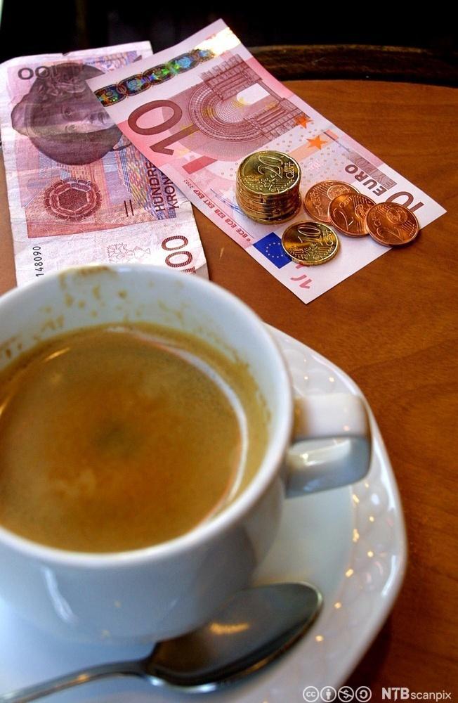 En kaffekopp på et bord med noen pengesedler ved siden. Foto.