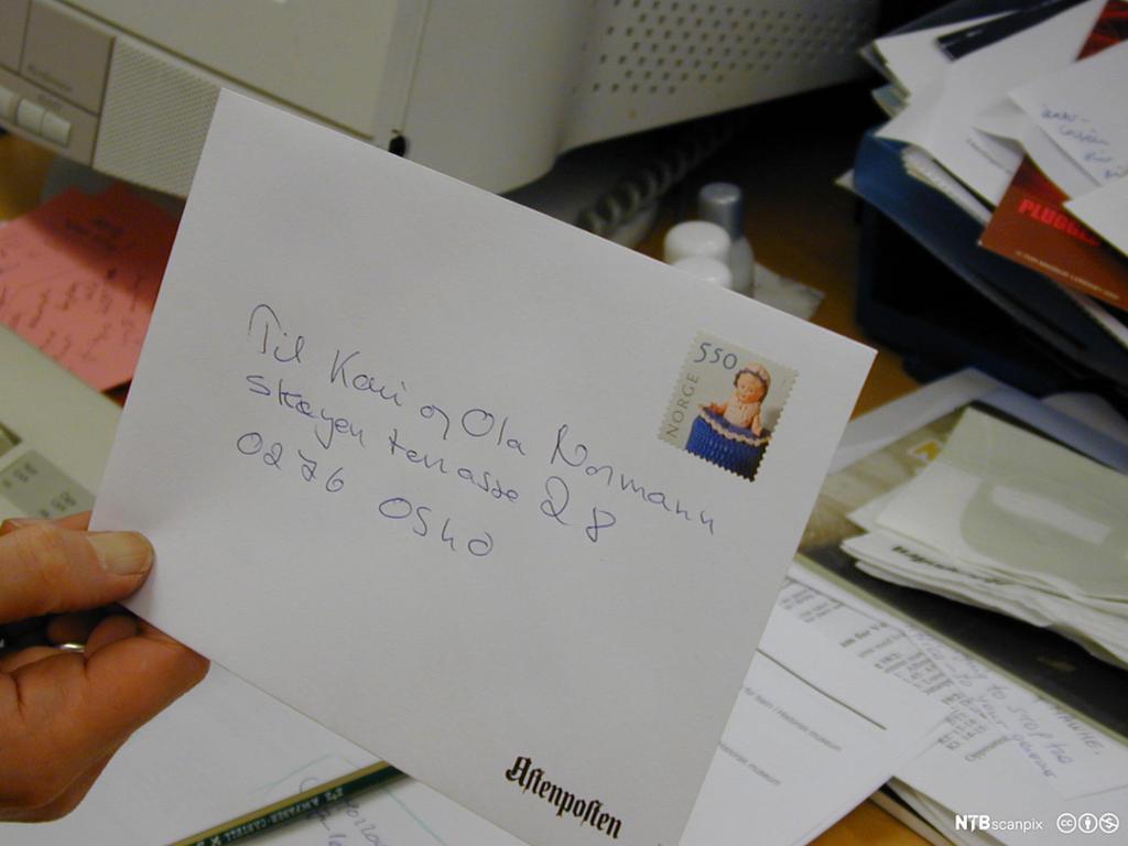 Nærbilde av hvit A5-konvolutt med handskrevet adresse og frimerke på.