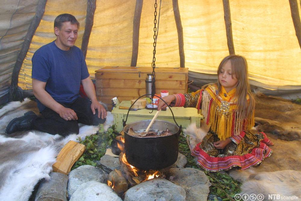 Ein same og ei lita samejente kokar reinsdyrkjøt i ei gryte på bålet. Foto