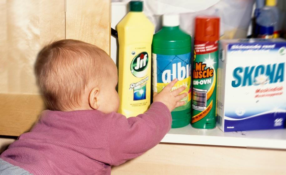 Baby griper etter en flaske vaskemiddel som står i et kjøkkenskap. Foto.
