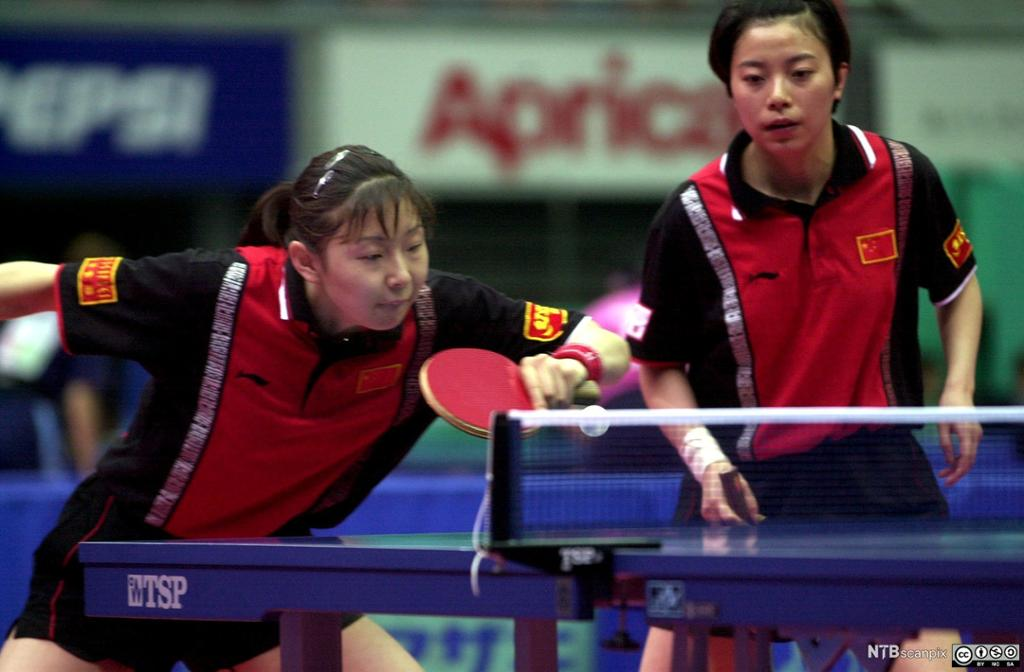 To kvinner spiller på lag i bordtennis. Foto.