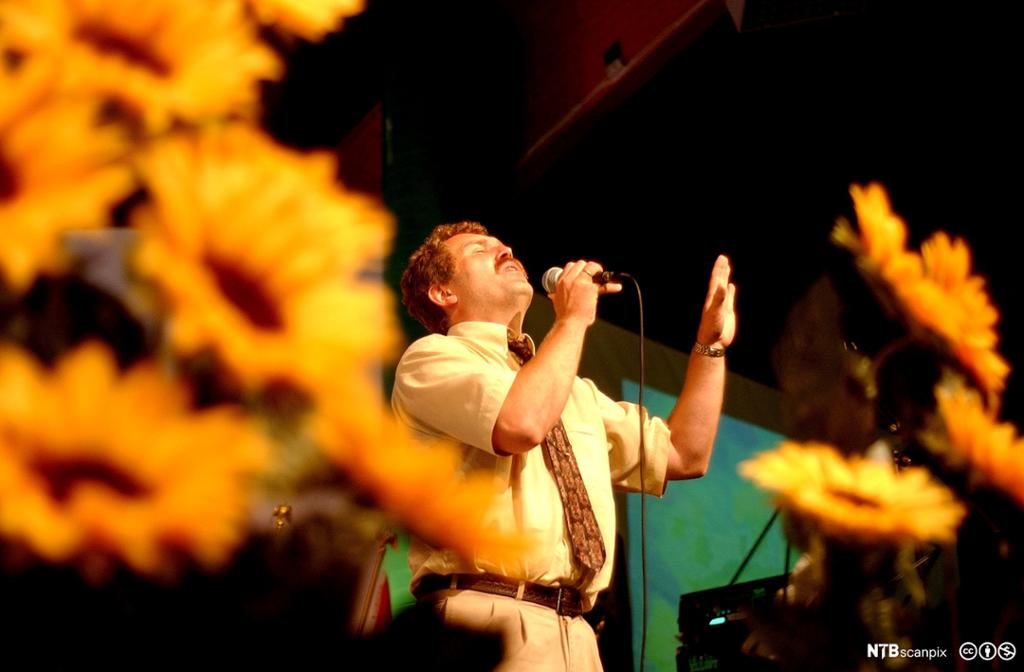 En engasjert mann med mikrofon taler til en forsamling. Foto.