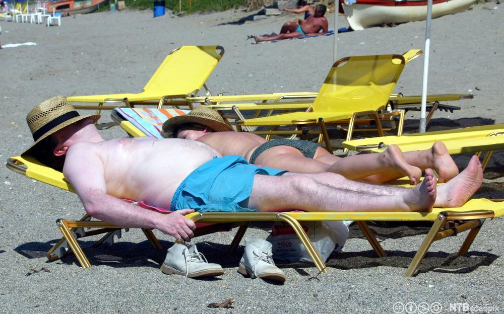 Hvit mann med solhatt på solseng. Foto.