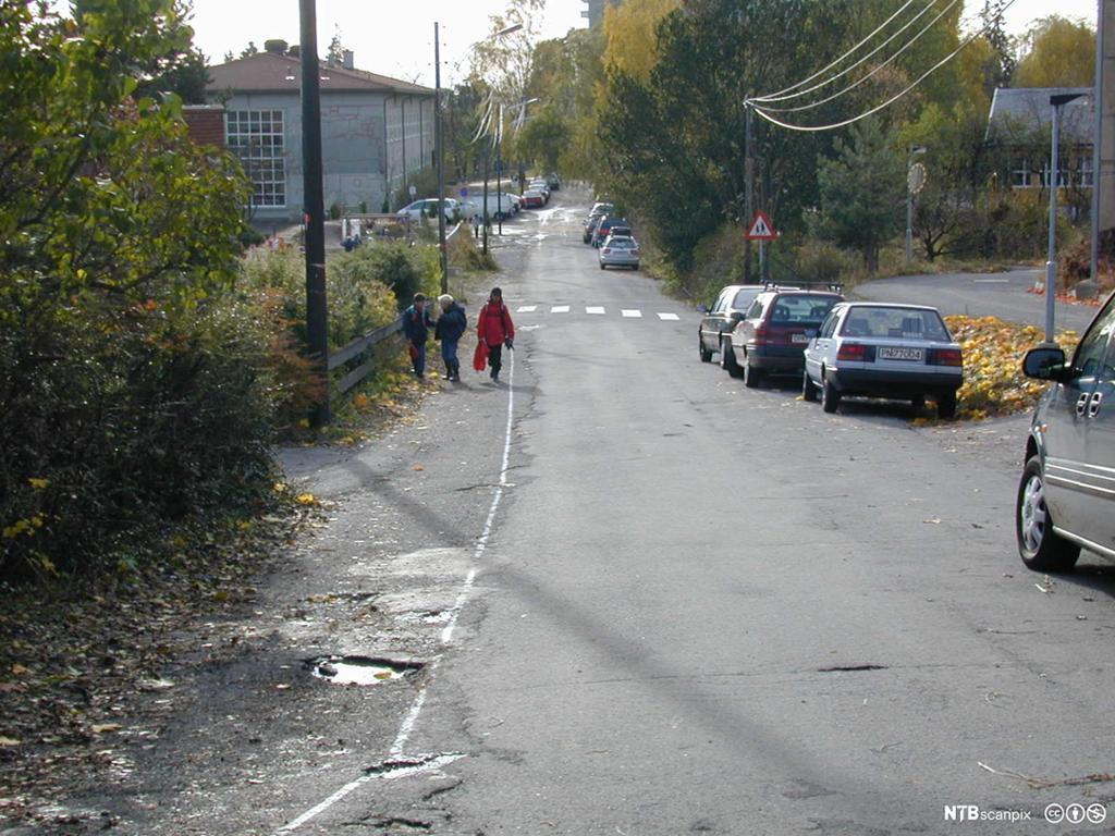 Oversiktsbilde av ei rolig bygate med biler parkert på den ene sida. Skolebarn går på motsatt side av gata. Foto.