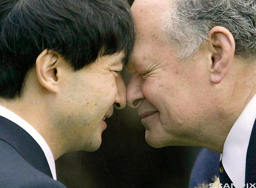 Menn hilser på hverandre ved å gni nesene mot hverandre. Foto.