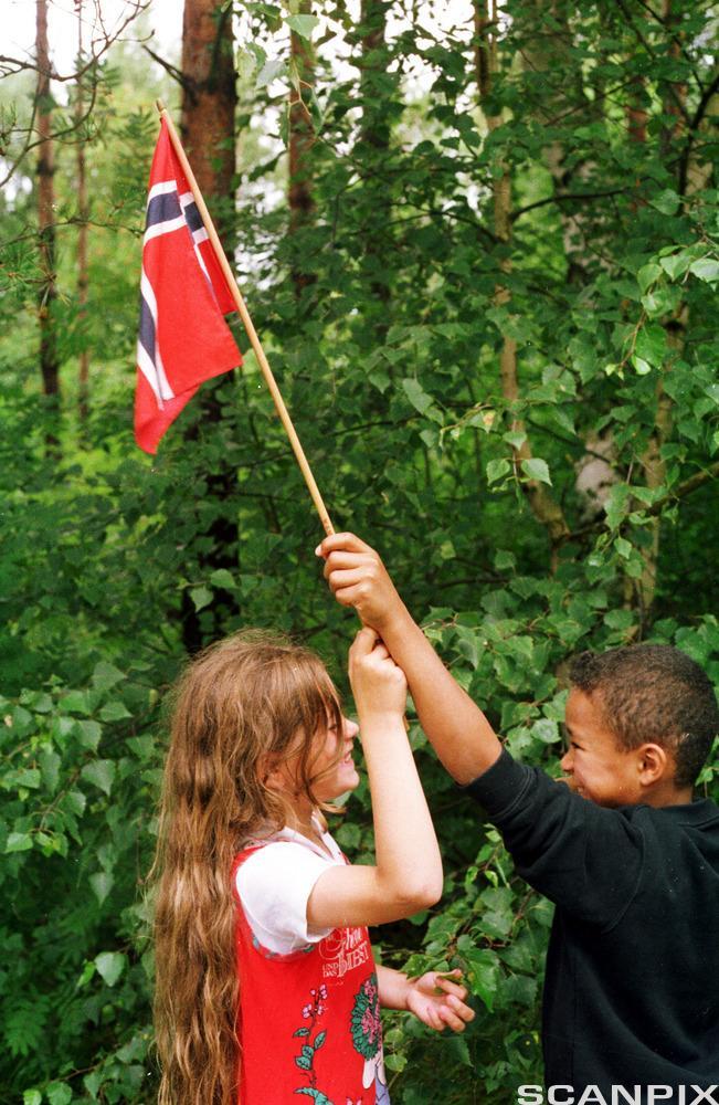 To barn holder et flagg sammen. Foto.