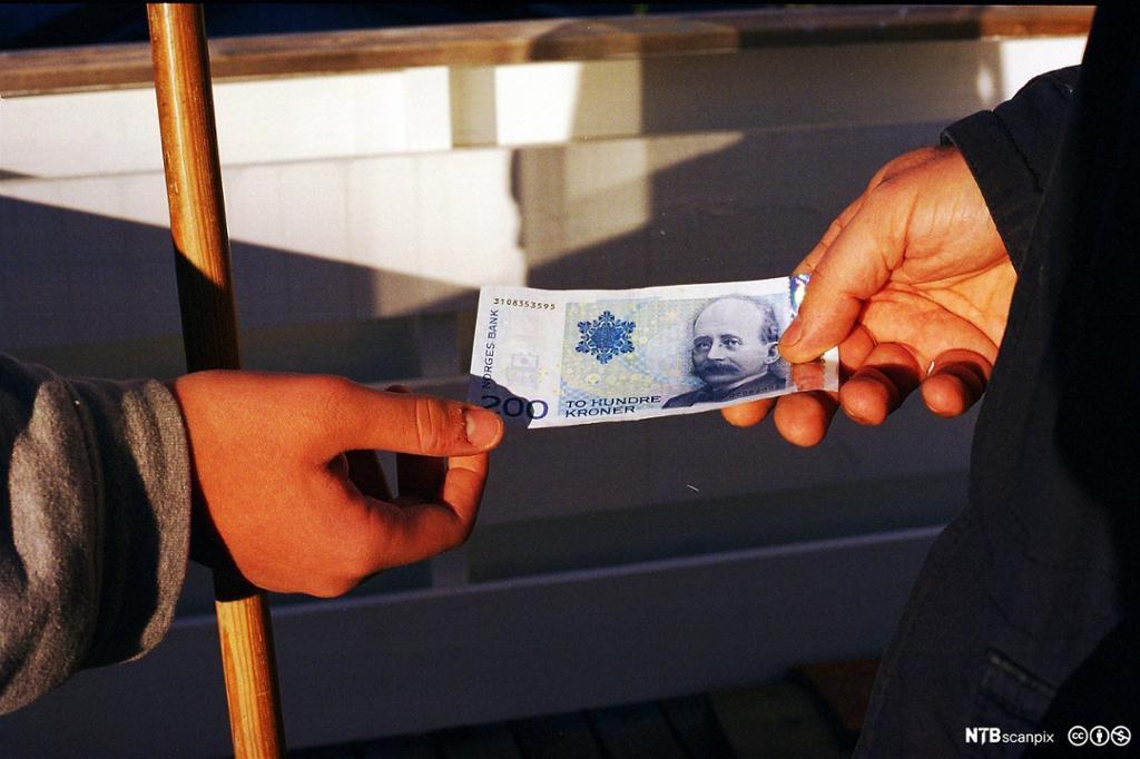 200 kroners seddel blir gitt fra en hånd til en annen. Foto.