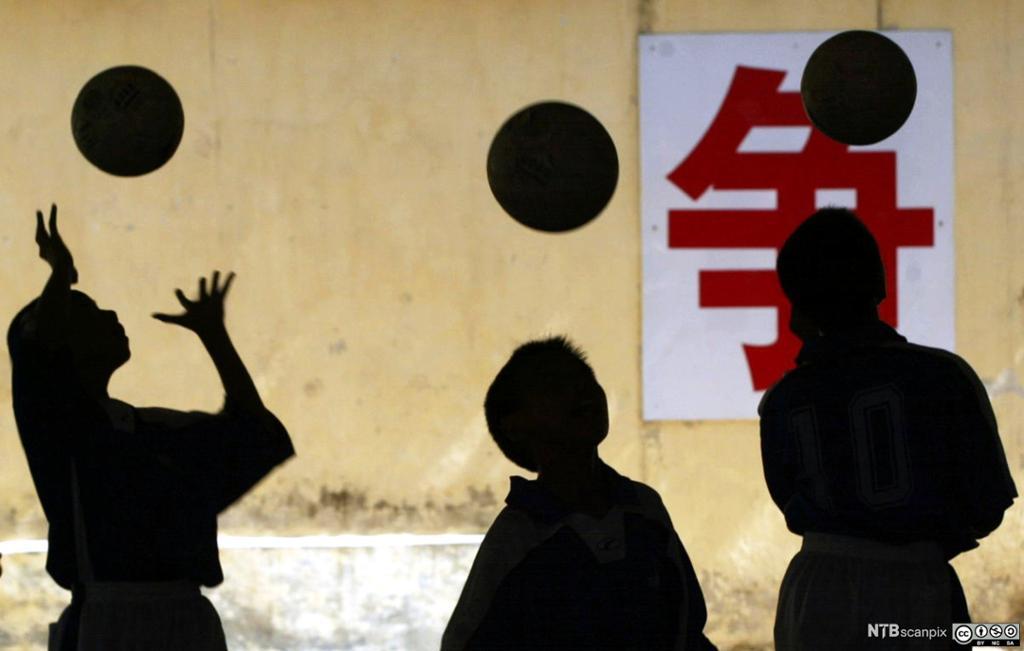 Kinesiske studenter trener fotballferdigheter foran et kinesisk tegn. Foto.