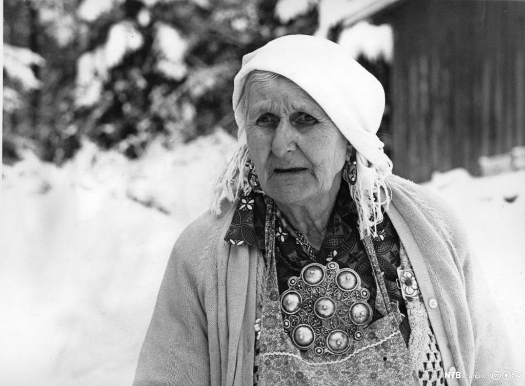 Jenny Emilie Pettersen, også kalt Tater-Milla, fotografert 86 år gammel i Våler. Hun har skaut, øredeobber og stor sølje. Foto.