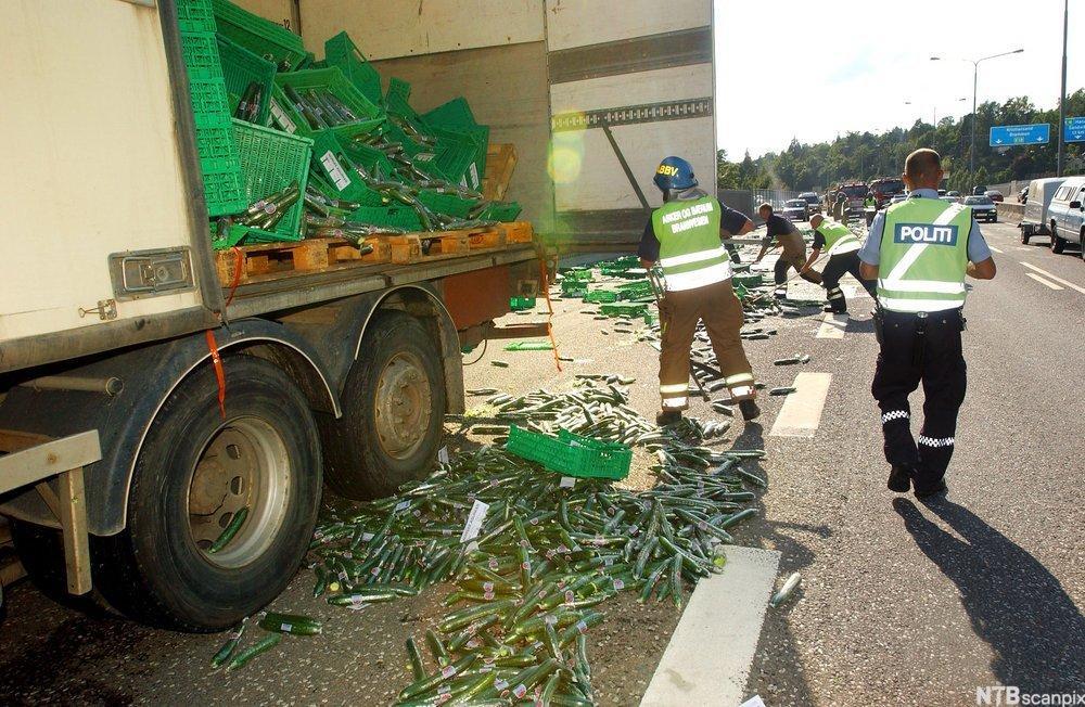 Lastebil med åpen dør og mange knuste varekasser i og utenfor.foto.