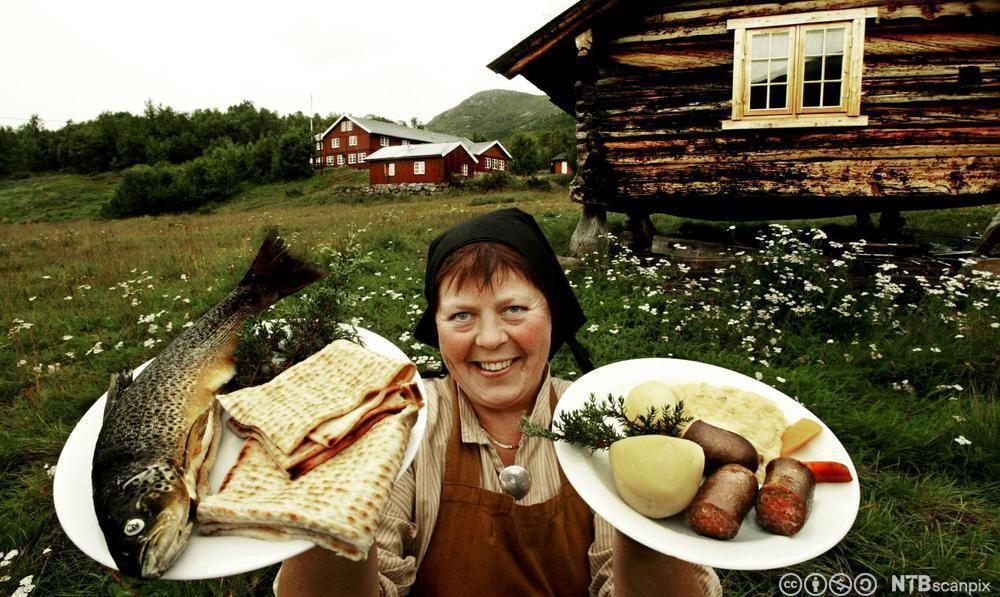 Bilde av en dame på en gård med to fat lokalmat. Foto.